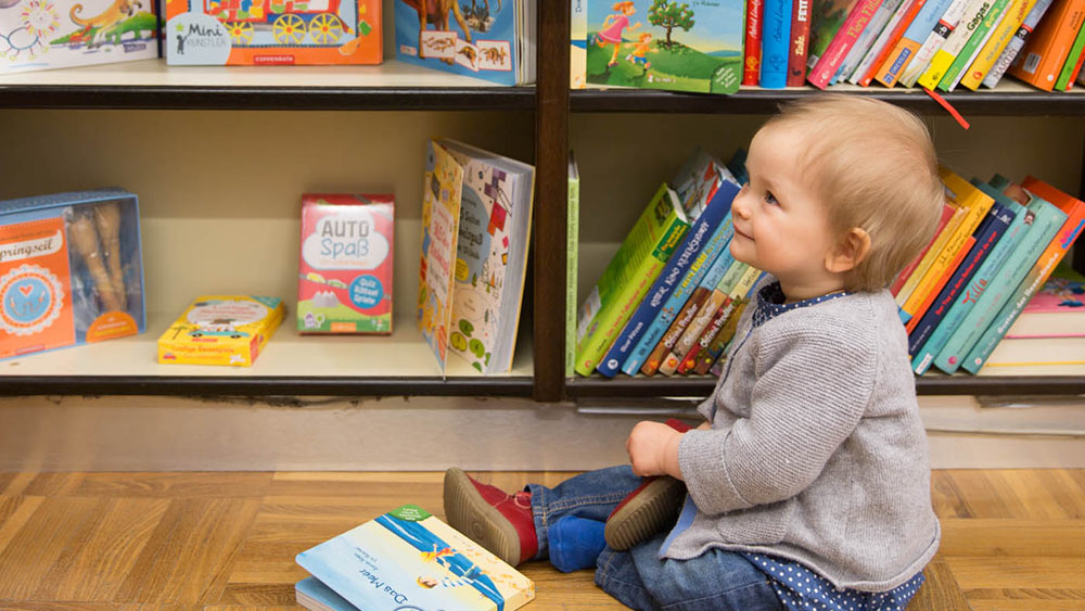Child checking out Cradle to Cradle certified books in a bookshop